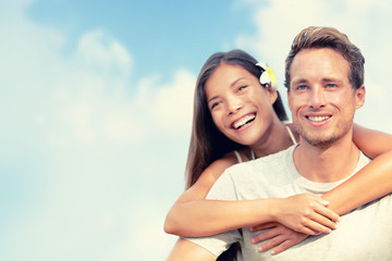 Happy couple hugging in summer blue sky background. Smiling young people tourists on travel vacation. Asian girl piggyback on man. Healthy lifestyle.