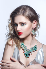 Beauty fashion portrait of an elegant girl with a sutured necklace.