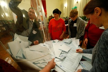 Members of a local election commission empty a ballot box before starting to count votes during the presidential election at a polling station in a settlement in Smolensk Region