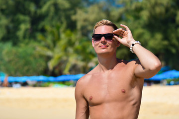 Sexy caucasian fit man in sun glasses posing at the beach. Handsome shirtless male portrait