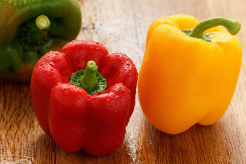 Green , yellow and red bell pepper with water drops closeup