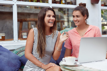 Happy women recreat in coffee shop, have fun together, surf in internet on laptop computer, enjoy hot aromatic cappuccino, have positive expressions. People, spare time and friendship concept.