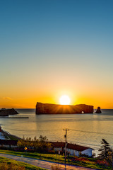 Famous Rocher Perce rock in Gaspe Peninsula, Quebec, Canada, Gaspesie region with cityscape at sunrise and sun, small town