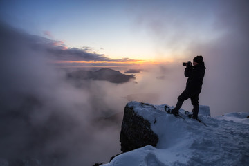 Adventurous man on the side of a steep cliff is taking pictures of the beautiful view during a vibrant sunset. Taken on top of St Mark's Peak, North of Vancouver, BC, Canada.