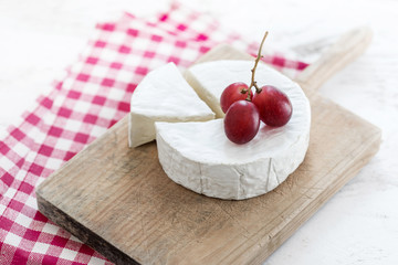 Soft Cheese wheel with a piece of cheese on a wooden board