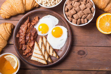 Breakfast with eggs , bacon and croissants