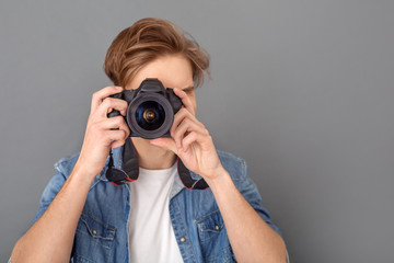 Young male photographer in jeans jacket studio isolated on grey taking photos close-up