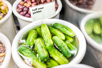 Closeup of plastic container jar filled with bulk green half sour pickles, mustard seeds in vinegar brine, sign