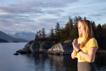Young girl in mediation positiong is enjoying the peaceful moment during sunset. Taken in Whytecliff park, Horseshoe Bay, Vancouver, BC, Canada.