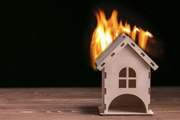 House fire concept. Toy house with flames