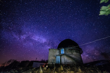 Night view of astronomical observatory against background of starry sky with milky way