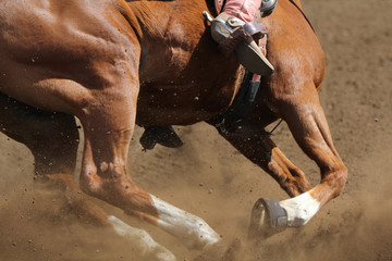 A close up view of a horse running in the dirt kicking up dust in a barrel race.
