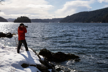 Photographer taking pictures of the beautiful landscape from Twin Island in Indian Arm, North of Vancouver, British Columbia, Canada.