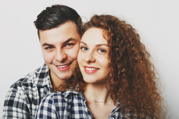 Close up of lovely family couple cuddle and look cheerfully at camera, celebrate their wedding anniversary, wear checkered shirts, isolated over white background. People, love and family concept