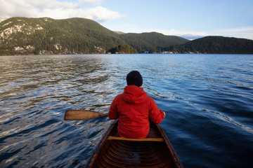 Man on a wooden canoe is paddling during a windy winter day. Taken in Indian Arm, North of Vancouver, British Columbia, Canada.