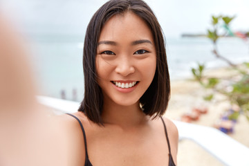 Pretty young Asian woman takes photo on camera og unrecognizable gadget, poses against sea or ocean horizon, takes picture during free time, enjoys good rest. Outdoor shot of cute Chinese girl