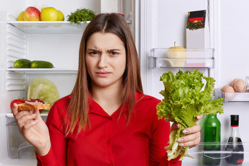 Discontent female frown face, has to keep to diet, eats only fruits and vegetables, holds lettuce and sandwhich in hands, stands at kitchen near refrigerator, has unhappy expression. Food concept