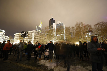 People watch illuminated Old Opera House during the Luminale, light and building event in Frankfurt