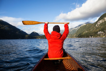 Man on a wooden canoe is holding his paddle up in the air. Taken in Indian Arm, North of Vancouver, British Columbia, Canada.