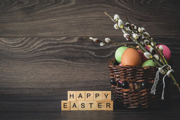 The inscription  happy Easter, made of light wooden cubes, painted eggs in a wicker basket and willow branches with seals on a dark wooden background