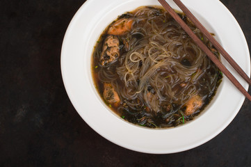 Japanese cuisine, soup with chashu pork, chives, sprouts, noodles and seaweed on the table under the sunlight. Old black rustic background. Top view