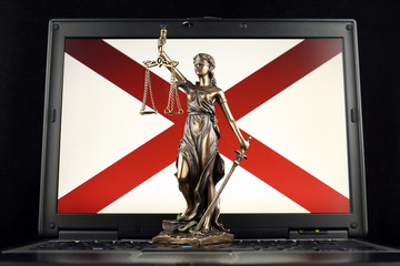 Symbol of law and justice with Alabama State Flag on laptop. Studio shot.