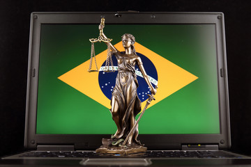 Symbol of law and justice with Brazil Flag on laptop. Studio shot.