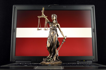 Symbol of law and justice with Latvia Flag on laptop. Studio shot.