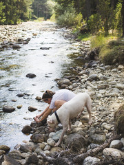 Female traveler and her boxer dog exploring a river