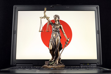 Symbol of law and justice with Japan Flag on laptop. Studio shot.