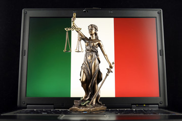 Symbol of law and justice with Italy Flag on laptop. Studio shot.