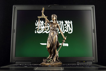 Symbol of law and justice with Saudi Arabia Flag on laptop. Studio shot.