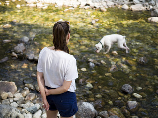 Young woman looking at her dog playing in the nature