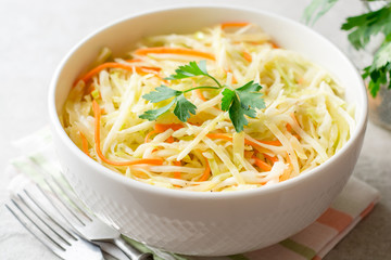 Fresh coleslaw salad in bowl on gray stone background.