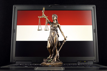 Symbol of law and justice with Yemen Flag on laptop. Studio shot.