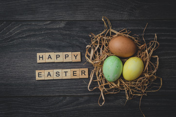 The inscription happy Easter, made of light wooden cubes, and 3 painted eggs in the nest on a dark wooden background