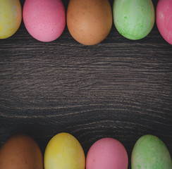 Easter concept: painted eggs on dark wooden background top view