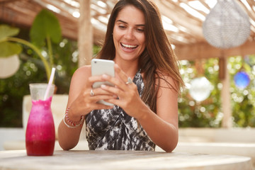 Photo of joyful lady with attractive look holds modern smart phone, reads pleasant message from friend or boyfriend while being on vacation in tropical country. Cute female uses electronic gadget