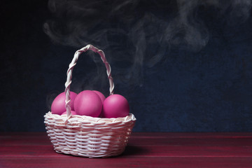 Painted eggs with steam in basket over dark background.