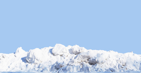Snow pile, hill. Large snow drift isolated on a blue sky background, close-up. Panoramic view. Winter in the mountains. Hummock, avalanche