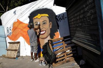 Street artist Aira Ocrespo paints a graffiti art in tribute of Rio de Janeiro city councilor Marielle Franco in Mare slums complex during a rally in Rio de Janeiro