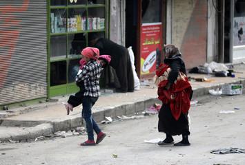Kurdish woman walks holding a blanket in Afrin