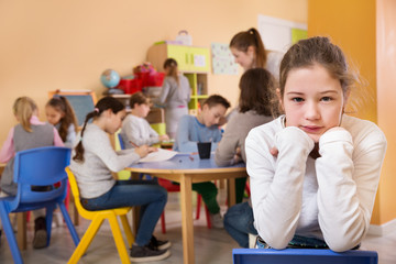 Upset girl in schoolroom on background with pupils