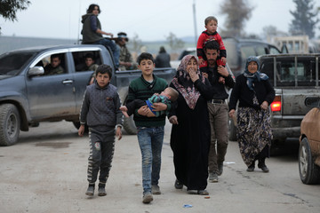 Kurdish boy holds his baby brother as he walks with his family in Afrin