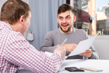 Satisfied man with partner working with documents at home