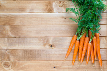 Carrot vegetable with leaves on the wooden background.