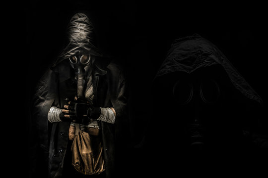 man in the gas mask in the hood, on the black background surrounded by smoke, with hands on the chest, survival soldier after apocalypse.