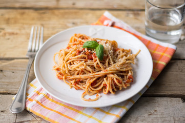 Homemade Italian pasta spaghetti with tomato sauce, fresh herbs and grated parmesan cheese on wooden rustic table