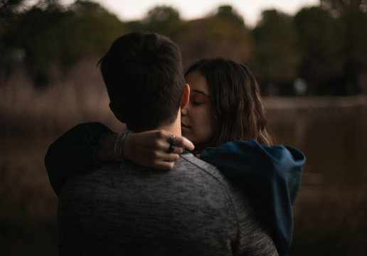 A cute spanish couple having a nice afternoon hugging and kissing each other in a park in front of a lake in Seville, Spain.