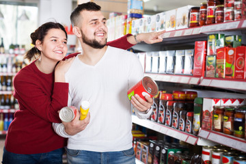 smiling couple choosing purchasing canned food for week at supermarket